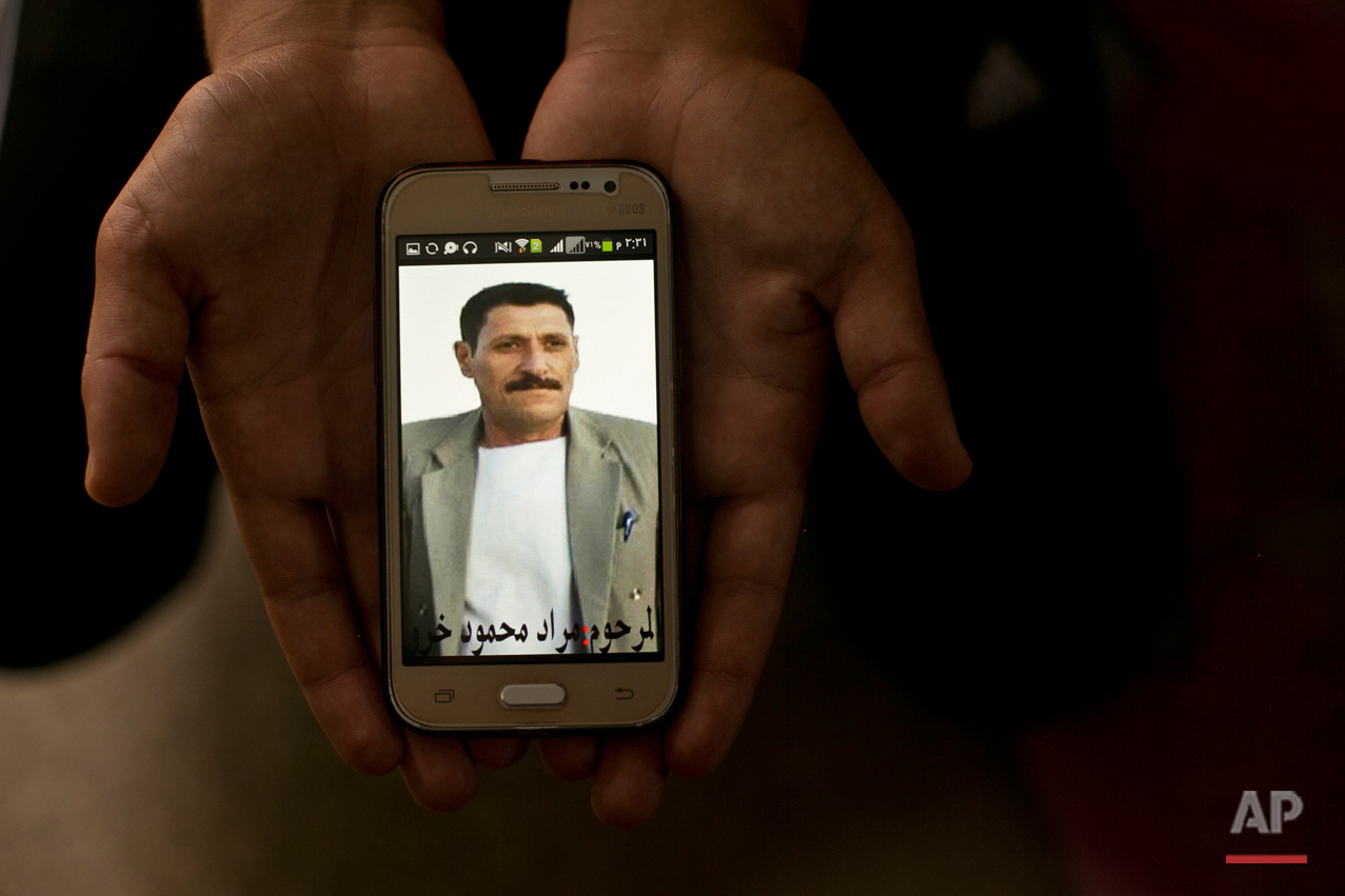 In this Wednesday, May 18, 2016 photo, a relative shows a phone picture of Murat Mahmoud during an interview with the Associated Press at Kankhe Camp for the internally displaced in Dahuk, northern Iraq. Murat was killed on Aug. 3, 2014 by Islamic State militants in a massacre of Yazidis and his body is among 40 believed in a mass grave at a farm on Sinjar Mountain. His daughter is still held by the militants. An analysis by The AP has found 72 mass graves left behind by Islamic State extremists in Iraq and Syria, and many more are expected to be discovered as the group loses territory. (AP Photo/Maya Alleruzzo)