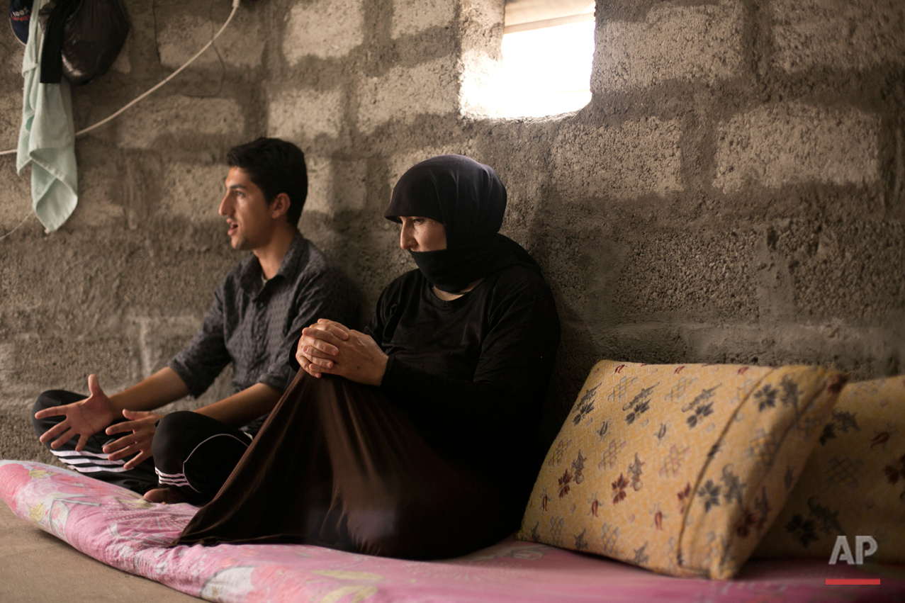 In this May 18, 2016 photo, Nouri, right, and her son speak to the Associated Press at Kankhe Camp for the internally displaced in Dahuk, northern Iraq. Her husband, Murat Mahmoud, was killed on Aug. 3, 2014, by Islamic State militants in a massacre of Yazidis. Their bodies are buried in a mass grave at the farm where they died, the family said. An analysis by The AP has found 72 mass graves left behind by Islamic State extremists in Iraq and Syria, and many more are expected to be discovered as the group loses territory. (AP Photo/Maya Alleruzzo)