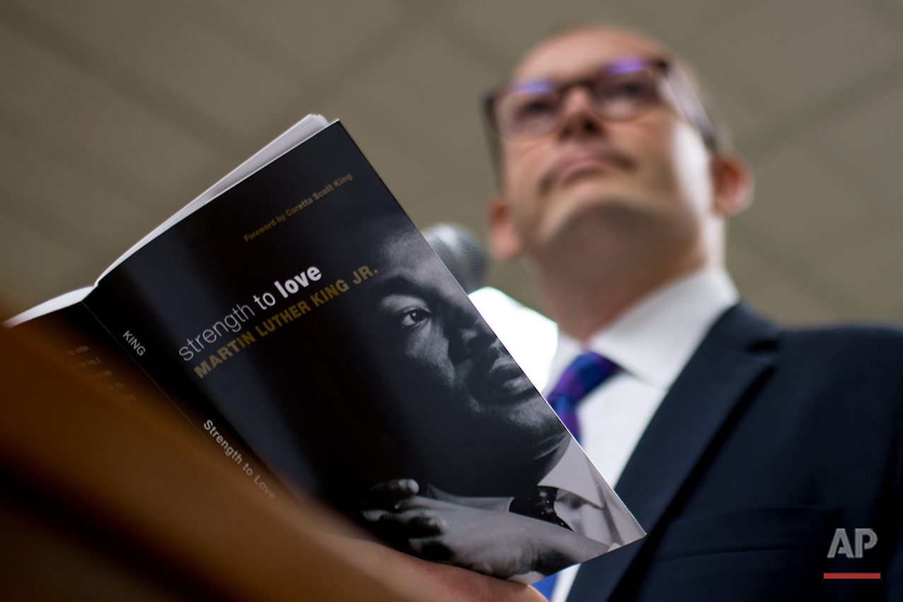 """The Rev. Scott Dickison teaches from a book of sermons by Martin Luther King Jr. during a Sunday School class at the First Baptist Church of Christ, a predominantly white congregation, in Macon, Ga., on Sunday, July 10, 2016. This class was held days after the fatal police shootings of Alton Sterling in Louisiana and Philando Castile in Minnesota, and the fatal ambush on Dallas police. """"It's weeks like these when we need more than ever to be with God's people,"""" Dickison told the roomful of congregants. (AP Photo/Branden Camp)"""