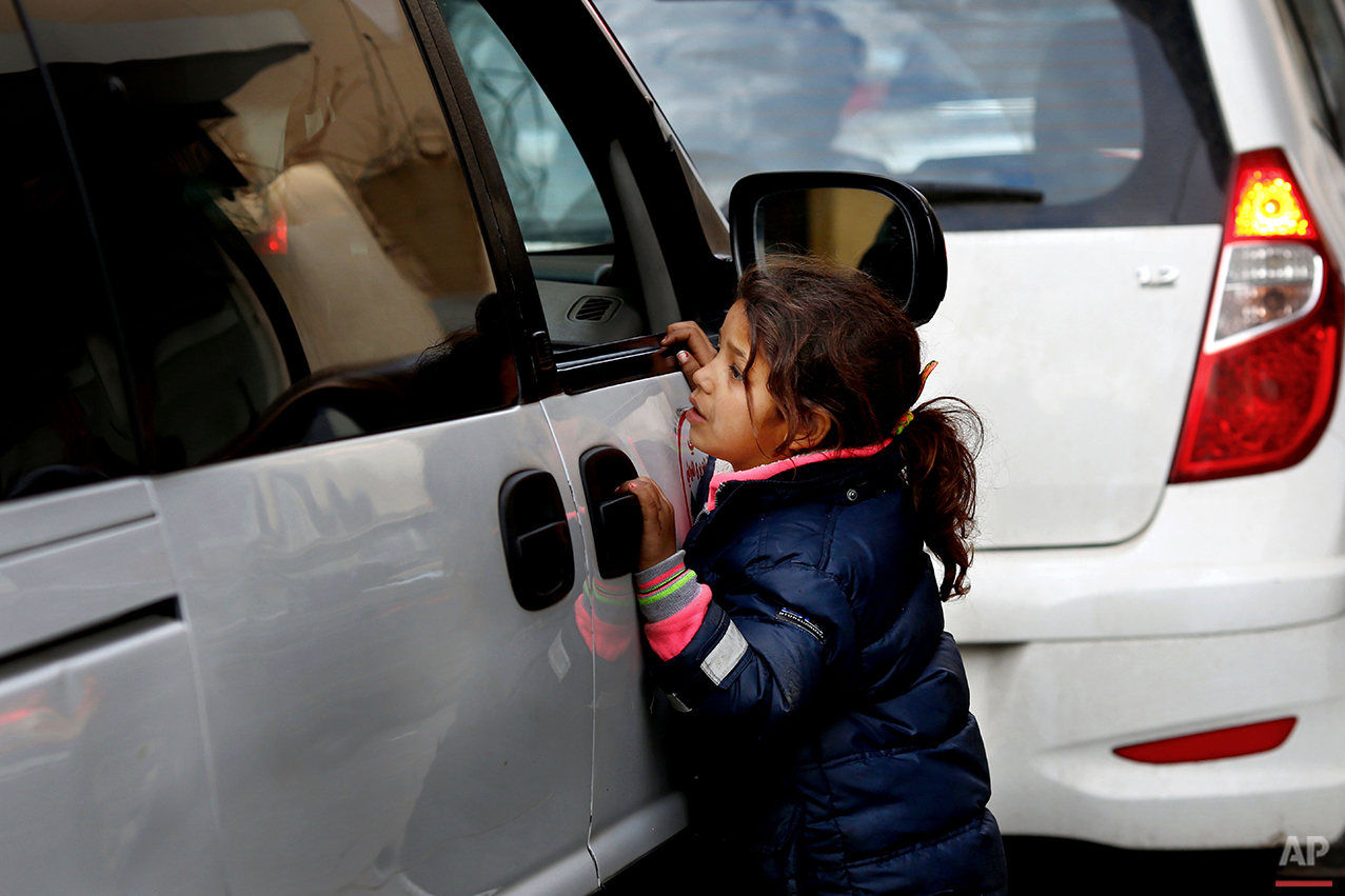 In this Wednesday, Feb. 10, 2016 photo, a Syrian refugee girl asks people in a car for money in traffic, in Beirut. A study published last year by the International Labor Organization, UNICEF and the Save the Children charity organization found there are more than 1,500 children living or working on Lebanon's streets, nearly three-quarters of them Syrian and most making a living by begging or roadside vending. (AP Photo/Hassan Ammar)
