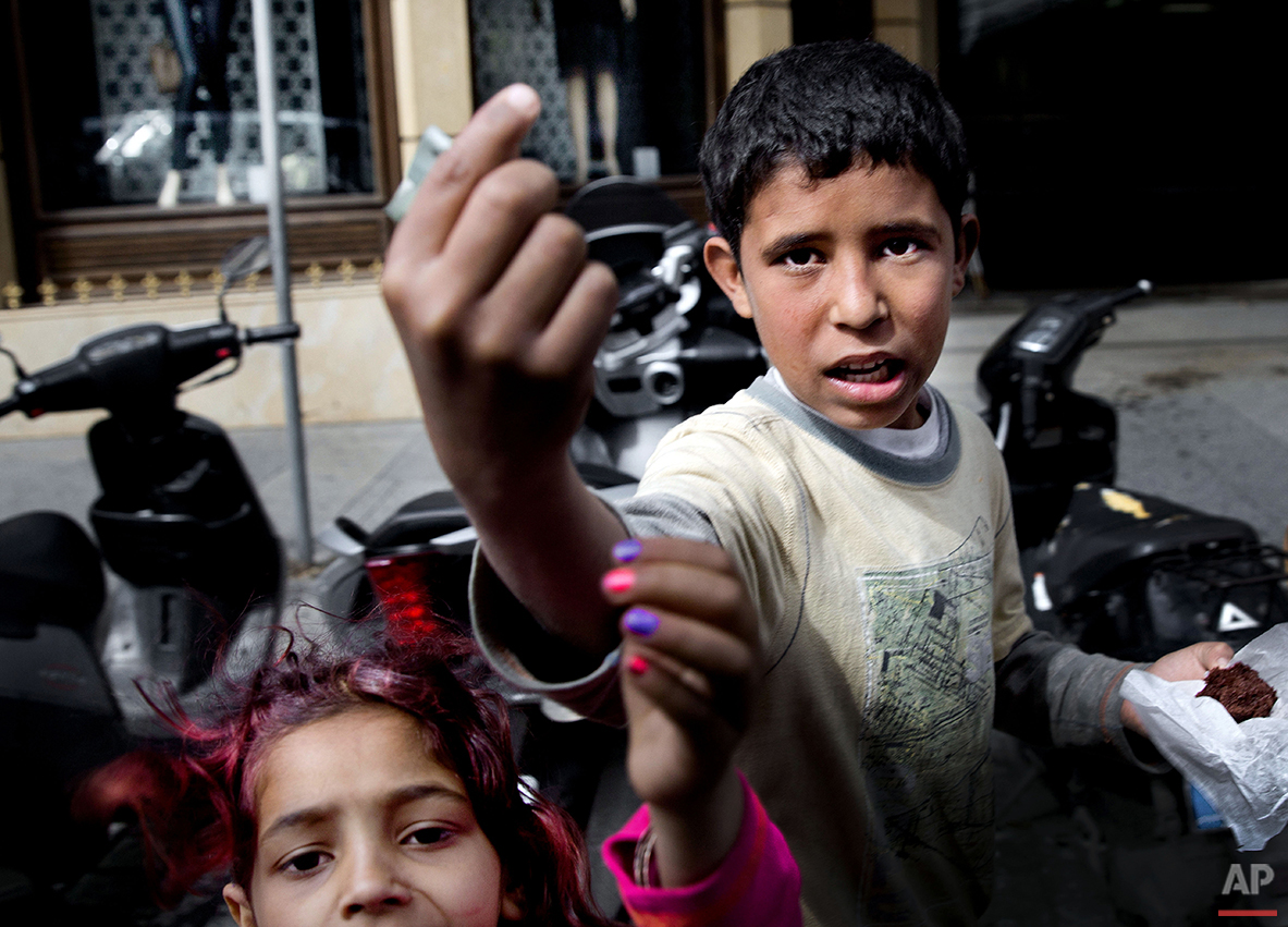 "In this Wednesday, March 16, 2016 photo, Syrian refugee Mohammad Hussein, 13, right, begs for money with his cousin, on a street in Beirut. Hussein is among the tens of thousands of Syrian children who fled the devastating war in their country to neighboring Lebanon, many of whom now are out of school and have to work to sustain their families. ""I wish I could go back to school, I liked school when I was in Syria,"" Hussein says. ""But now I can't, I am the eldest and I must support my mother and sisters."" (AP Photo/Hassan Ammar)"