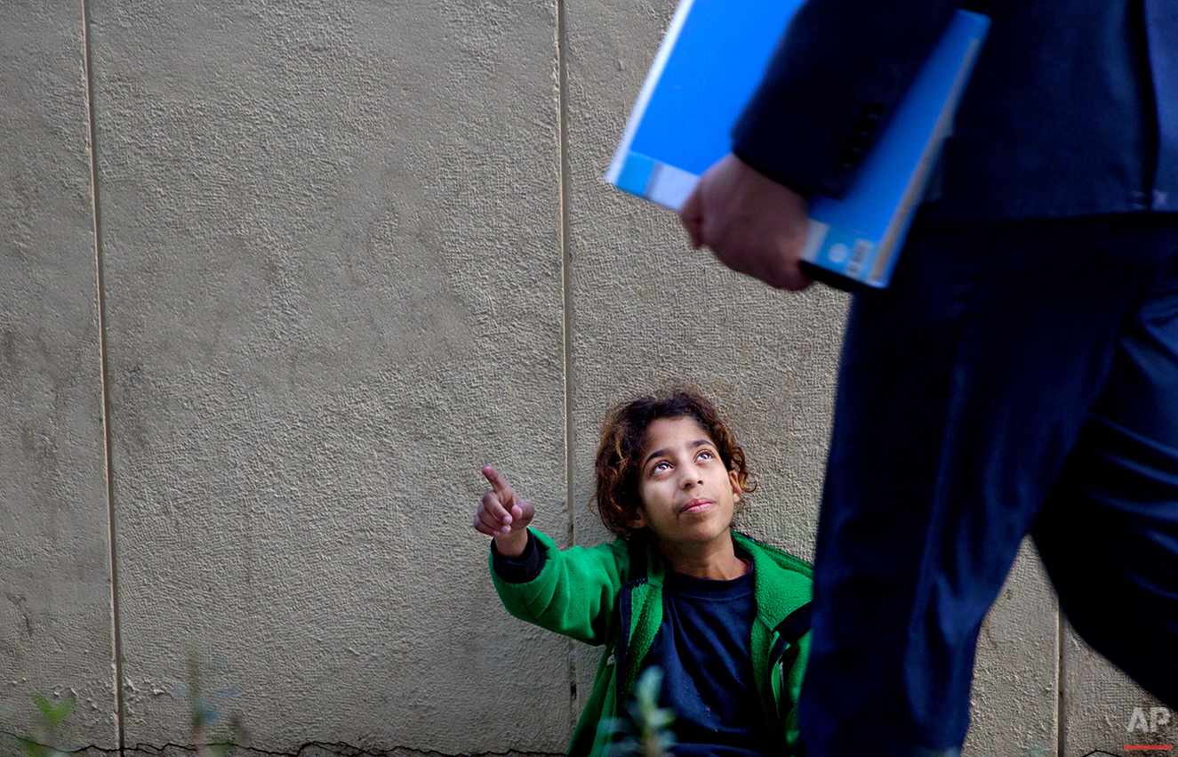 In this Wednesday, March 16, 2016 photo, a Syrian refugee girl begs for money on a sidewalk outside a hospital in Beirut. It is one of the most visible signs of the refugee crisis that has put an immense strain on neighboring countries and destabilized Europe. On Lebanon shopping streets, roundabouts and traffic lights, child beggars are seen pressing their small faces against windows of cars, stretching their hands for money or selling chewing gum or flowers. (AP Photo/Hassan Ammar)