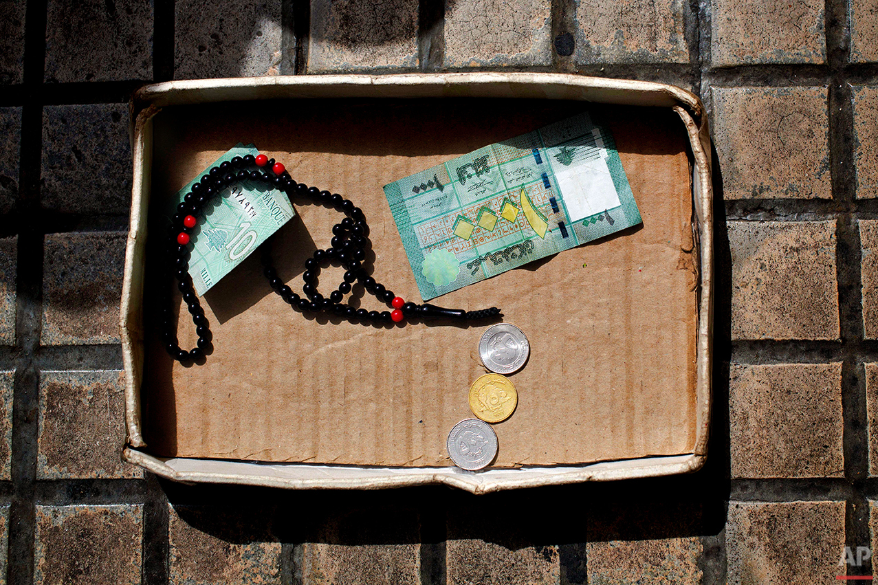 This Friday, March 25, 2016 photo, shows a cardboard box with money and praying beads belonging to a Syrian refugee woman who fled form her hometown Aleppo, on a sidewalk in Beirut. Begging is one of the most visible signs of the refugee crisis that has put an immense strain on neighboring countries and destabilized Europe. On Lebanon shopping streets, roundabouts and traffic lights, child beggars are seen pressing their small faces against windows of cars, stretching their hands for money or selling chewing gum or flowers. (AP Photo/Hassan Ammar)