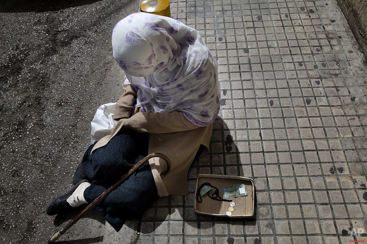 In this Friday, March 25, 2016 photo, a Syrian refugee woman, who fled her hometown Aleppo, begs for money on a sidewalk, in Beirut. Lebanon is home to more than 1 million registered Syrian refugees, or nearly a quarter of the country's 4.5 million people, the highest refugee population in the world per capita. (AP Photo/Hassan Ammar)