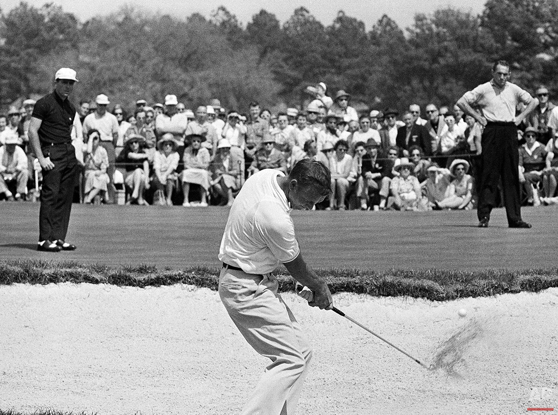In this April 9, 1962 photo, Arnold Palmer hits from a sand trap on the second hold during a playoff in the Masters golf tournament in Augusta, Ga., as Gary Player, left, and Dow Finsterwald look on.  Palmer claimed his third green jacket by winning the three-way playoff. (AP Photo/File)