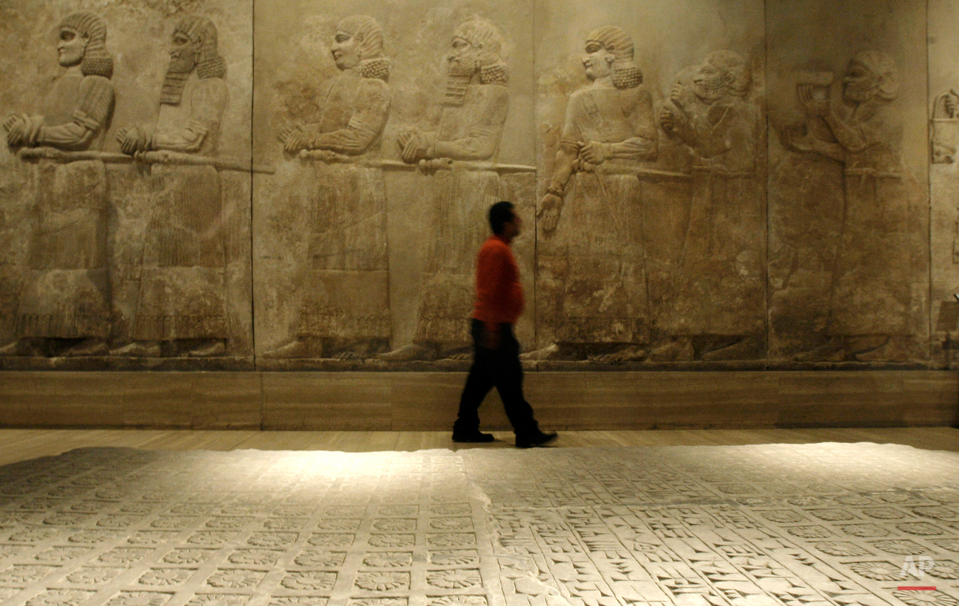 A guard looks up at an Assyrian relief sculpture inside Iraq's national museum, in Baghdad, on Tuesday, Nov. 24, 2009. Google is documenting the treasures of Iraq's national museum, home to priceless artifacts from the Stone Age through Islamic periods, and will make the photographs available online early next year, the company's chairman said Tuesday. (AP Photo/Petros Giannakouris)
