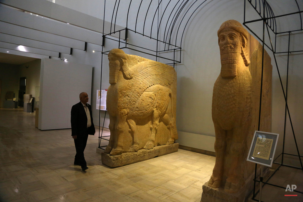 """In this March 1, 2015,photo, Aaman at Iraq's National Museum in Baghdad walks past two ancient Assyrian winged bull statues. Islamic State militants """"bulldozed"""" the renowned archaeological site of the ancient city of Nimrud in northern Iraq on Thursday, March 5, 2015, using heavy military vehicles, the government said. Nimrud was the second capital of Assyria, an ancient kingdom that began in about 900 B.C., partially in present-day Iraq, and became a great regional power. The city, which was destroyed in 612 B.C., is located on the Tigris River just south of Iraq's second largest city, Mosul, which was captured by the Islamic State group in June. (AP Photo/Karim Kadim)"""