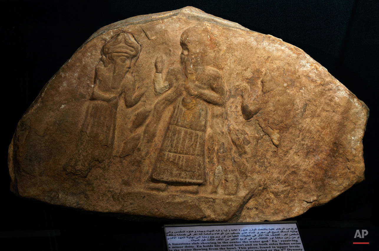 In this picture taken on Tuesday, April 2, 2013 a limestone slab showing in the center the water god, Ea, receiving a minor deity, is displayed at the national museum in Baghdad, Iraq. Ten years after Iraqís national museum was looted and smashed by frenzied thieves during the U.S.-led invasion in 2003 to topple Saddam Hussein, itís still far from ready for a public re-opening. Work to overcome decades of neglect and the destruction of war has been hindered by power struggles, poorly-skilled staff and the persistent violence plaguing the country, said Bahaa Mayah, Iraqís most senior antiquities official. (AP Photo/Hadi Mizban)