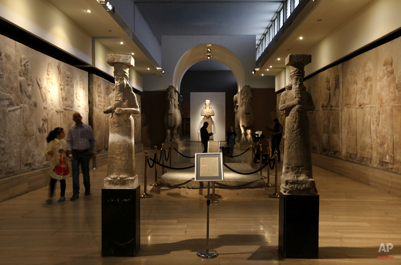 In this Monday, March 7, 2016 photo, Iraqis visit the Assyrian Hall surrounded by ancient artifacts of at the Iraq National Museum in Baghdad. After the destruction wreaked on archaeological sites by Islamic State group, the collections at the Iraq's National Museum in Baghdad have become even more important. It's now one of the places you can find relics from ancient cities that fell into the extremists' hands. As many as 4,000 archaeological sites are still under the domination of IS and around 100 sites have been destroyed, according to Iraqi Culture Minister Firyad Rwandzi. (AP Photo/Hadi Mizban)
