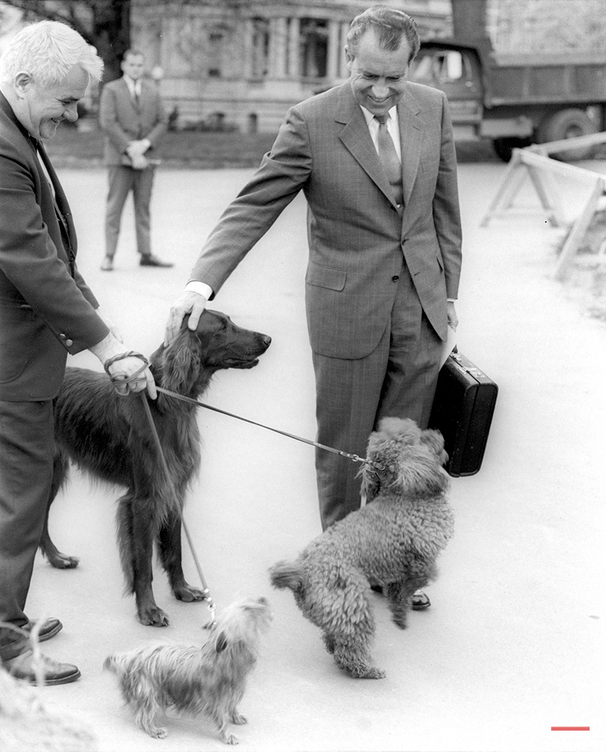 U.S. President Nixon pats the head of his Irish Setter pet King Timahoe as he walks from his office in the Executive Office building to the White House in Washington D.C. on April 30, 1970.  White House electrician Traphes Bryant holds back the other first family pets Pasha, a Yorkshire Terrier, and Vickie, a miniature French Poodle.  (AP Photo)