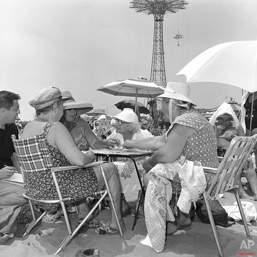 Within feet of the cool Atlantic surf four women play a hot game of gin rummy on the sands of Coney Island, New York on July 23, 1961. (AP Photo/Jack Kanthal)