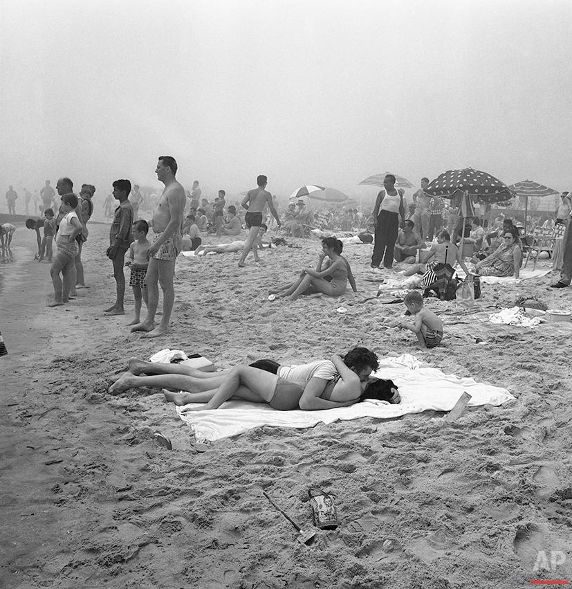 A summer romance blossoms on the beach at Coney Island, New York, July 27, 1961. (AP Photo/John Lindsay)