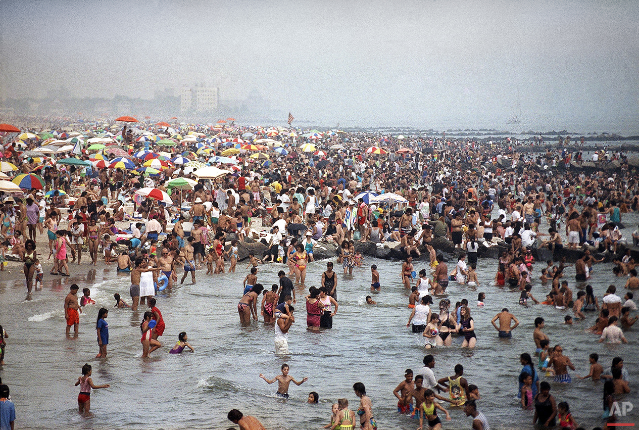 Crowds of people swarm to the beach at Coney Island in Brooklyn on July 21, 1991 in an effort to find relief from temperatures that swarmed over the 100-degree mark in New York City. (AP Photo/Mike Alexander)