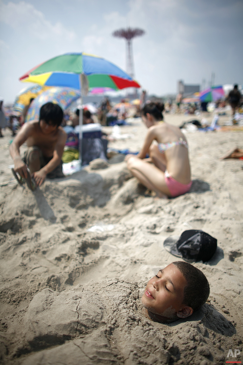 Only his face exposed to the sun, Brian Suarez, 9, stays cool by staying underground on the beach at Coney Island Wednesday, Aug. 2, 2006 in the Brooklyn borough of New York. (AP Photo/Jason DeCrow)