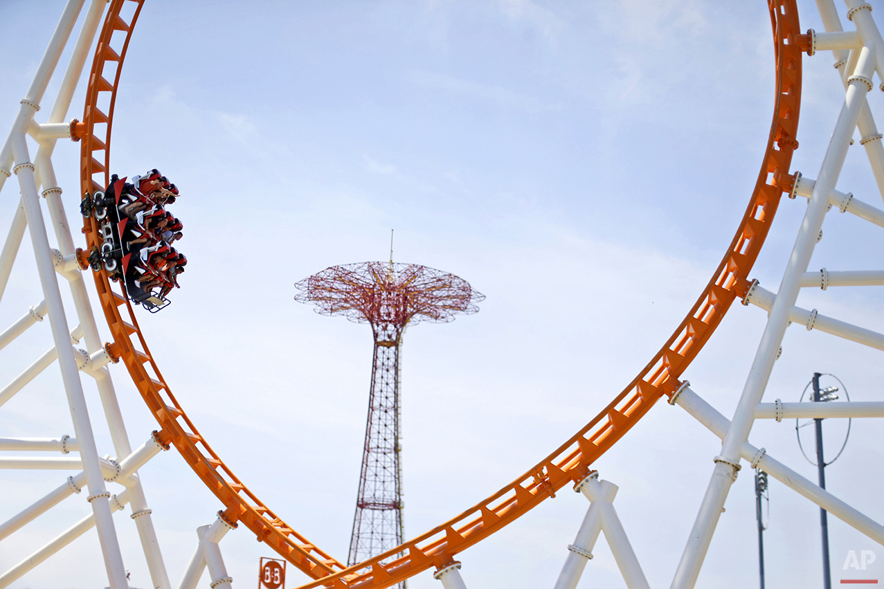 Visitors to Coney Island ride the Thunderbolt, Friday, July 3, 2015, in the Brooklyn borough of New York. (AP Photo/Mary Altaffer)