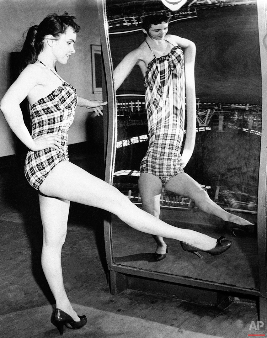 Looks as if Sybil Scotford is wearing one of those new chemise swimsuits until you see it outside the funny mirror at Coney Island, New York on July 1, 1958. (AP Photo)