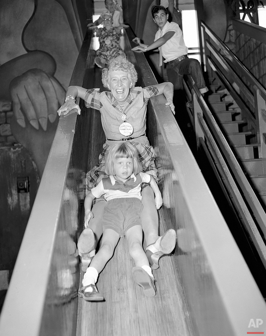 Grandma Margaret Mackenzie has three-year-old Janie Watt along for company as they are whisked down a slide at Steeplechase Park in New York on August 13, 1954. (AP Photo/Carl Nesensohn)