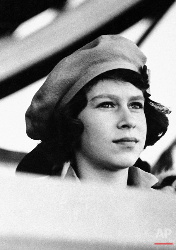 """Her Royal Highness Princess Elizabeth Alexander Mary, eldest child of the King and Queen of England, is 16 years old on April 7, 1942. Like thousands of other children, the Princess will probably observe the occasion quietly """"somewhere in the country."""" Since the war, she has been knitting garments for the poor, contributing funds to purchase cigarettes for the armed forces and attending dances and armed forces and attending dances and programs of evacuated children.  Other years it was different.   In 1937 Princess in review at Portsmouth, spoke over the radio and appeared at public functions. When her parents toured American in 1939 she had the time of her life.   She was appointed recently a colonel in the Grenadier Guards. (AP Photo)"""