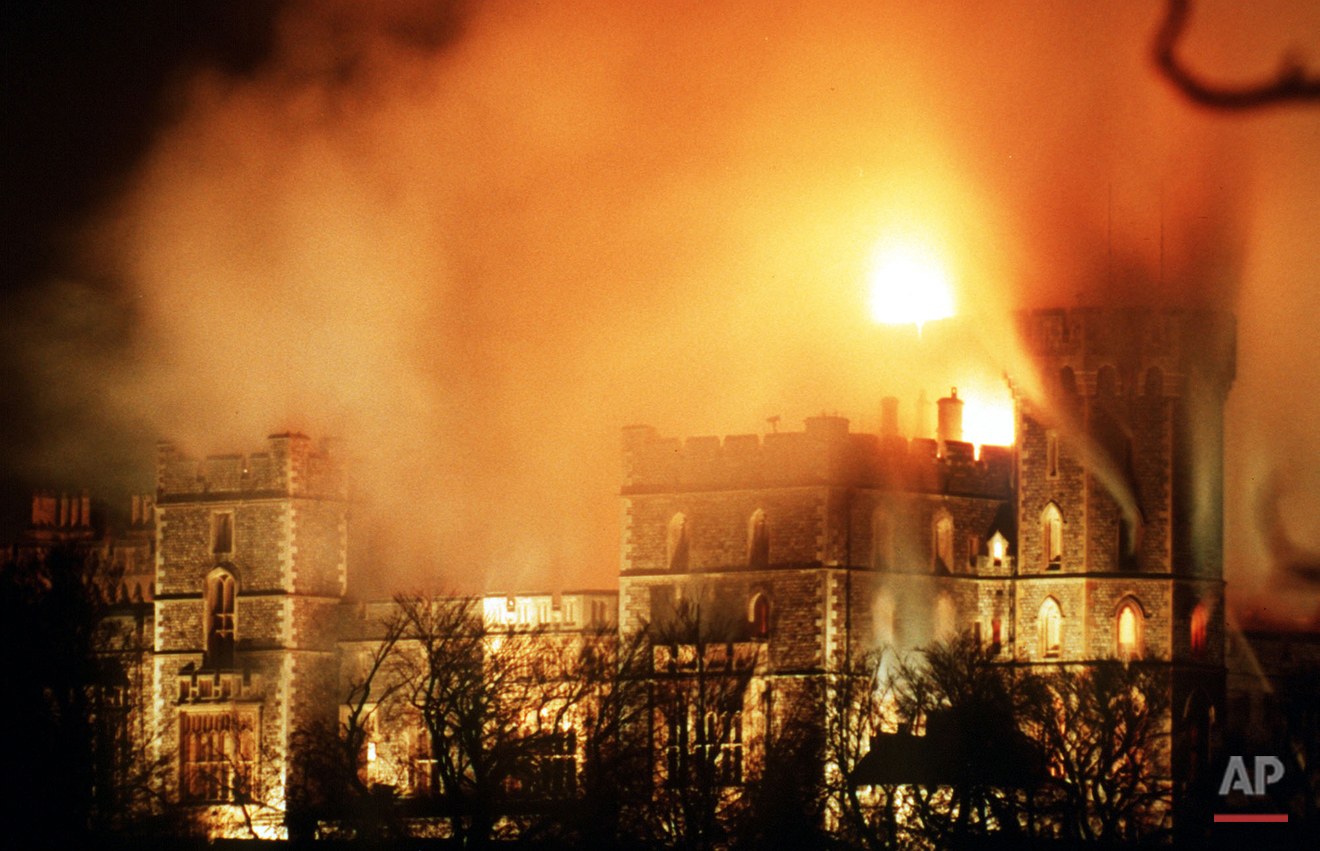 Hours after the major fire started flames continue to rise over Windsor Castle, causing millions of pounds of damage. (AP Photo/Denis Paquin)