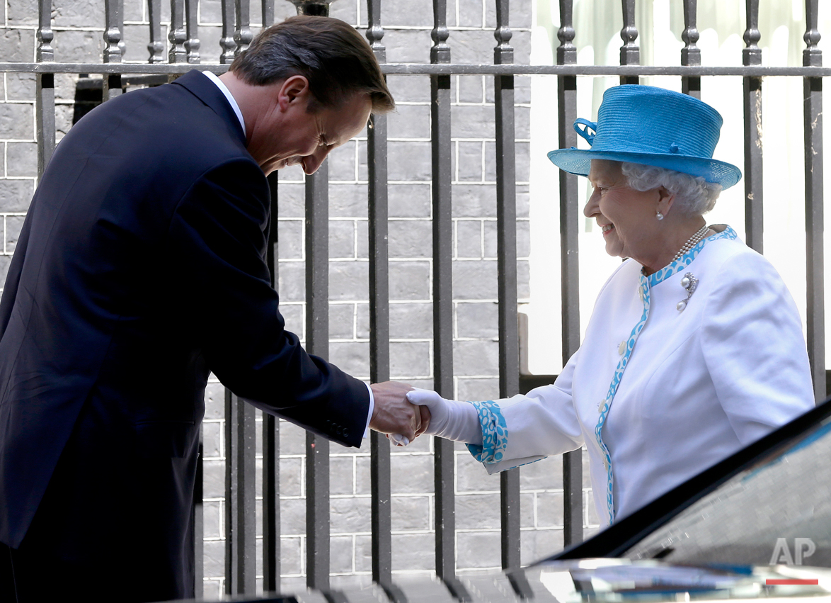 Britain's Queen Elizabeth II, right, is greeted by Britain's Prime Minister David Cameron,  as she arrives for lunch at Downing Street in London, Tuesday, July 24, 2012.  The Prime Minister is hosting a lunch at Downing Street for The Queen and the Duke of Edinburgh with the Deputy Prime Minister and former Prime Ministers including Sir John Major, Tony Blair and Gordon Brown. (AP Photo/Kirsty Wigglesworth)