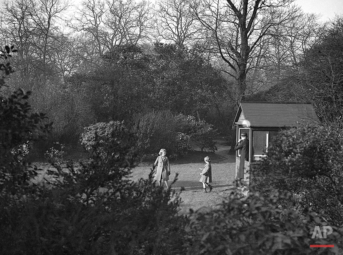 Princess Elizabeth, left, and Princess Margaret Rose playing in the garden of No. 145 Piccadilly, London, in the warm December sun, on Dec. 19, 1936. (AP Photo)