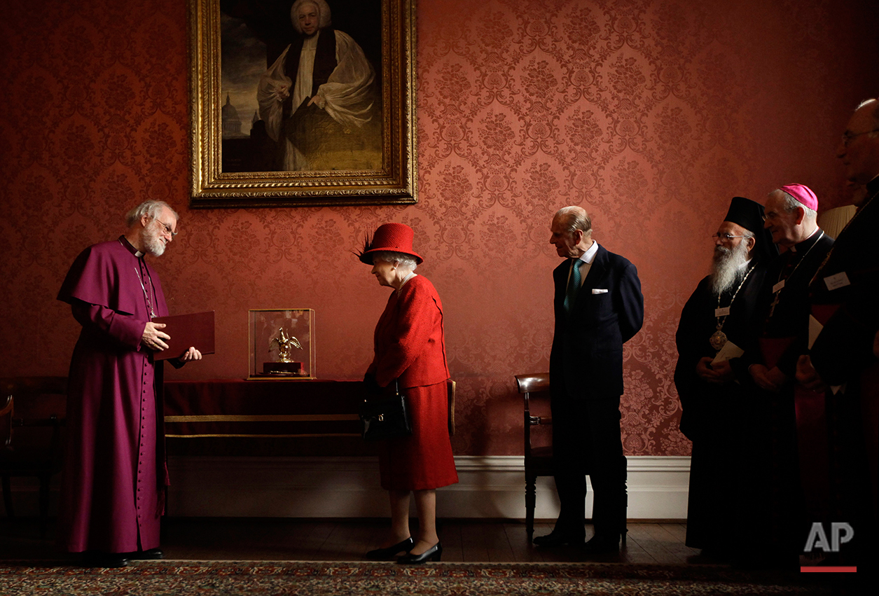 Britain's Queen Elizabeth II, second left, is shown the Ampulla and Coronation Spoon used at her coronation in 1953 by the Archbishop of Canterbury Rowan Williams, left, as her husband Prince Philip, third from left, and other Christian guests watch as they attend a multi-faith reception to mark the Diamond Jubilee of the Queen's Accession at Lambeth Palace in London, Wednesday, Feb. 15, 2012. (AP Photo/Matt Dunham-Pool)