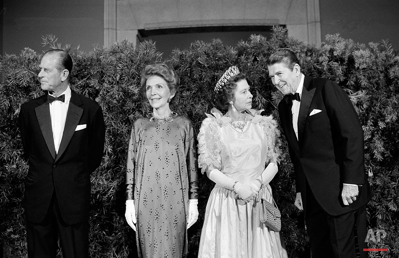 President Ronald Reagan listens as he poses for photographers with Queen Elizabeth II at a formal state dinner, March 3, 1983, at the M.H. de Young Museum in San Francisco's Golden Gate Park.  At left are Prince Philip and first lady Nancy Reagan.  (AP Photo/Ed Reinke)