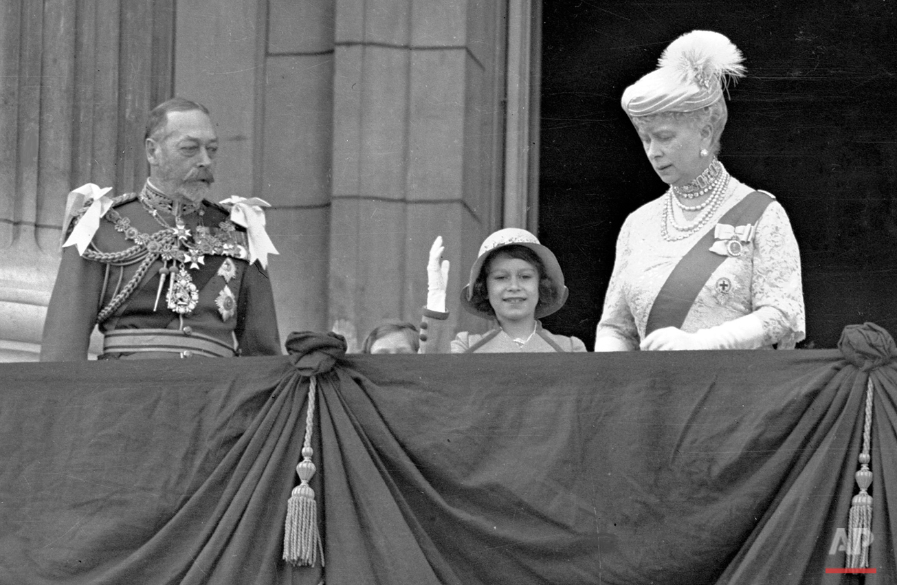 Britain's Queen Elizabeth II, then Princess Elizabeth, centre, waves as she stands on the on the balcony of Buckingham Palace, London, with her grandparents King George V and Queen Mary, in this May 6, 1935 photo. Princess Margaret is just visible over the balcony edge.  The Queen will celebrate her 80th birthday on April 21, 2006. (AP Photo)