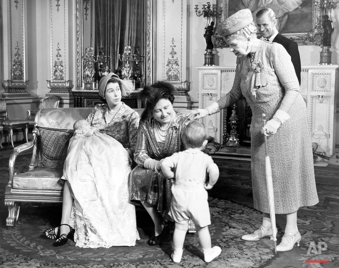Prince Charles, two-year-old son of Princess Elizabeth and the Duke of Edinburgh, seems to be the center of attraction at Buckingham Palace in London on Oct. 22, 1950, when his two-month-old sister, Princess Anne, was christened. Here the young Prince walks to his grandmother, Queen Elizabeth (seated right) and his great-grandmother, Queen Mary (right). Princess Elizabeth holds the infant Princess Anne while the Duke of Edinburgh watches proceedings from the rear. (AP Photo)