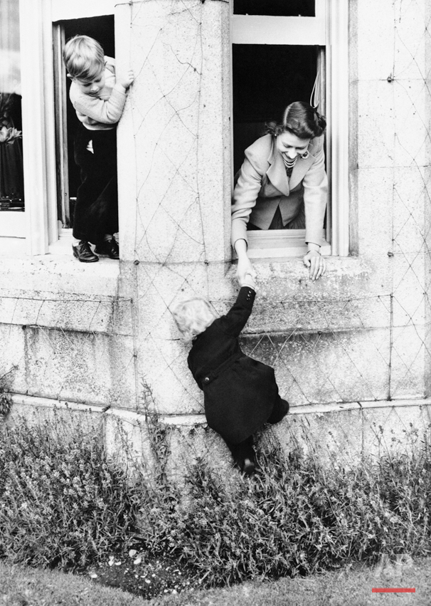 Queen Elizabeth II, right, shown playing with her two children, Prince Charles, left, and Princess Anne, climbing, at Balmoral Castle the Royal Residence on the River Dee, May 1, 1952, West Aberdeenshire, Scotland. (AP Photo)