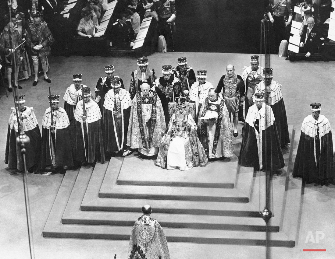 Surrounded by peers and churchmen, Queen Elizabeth II sits on throne in Westminister Abbey, London, June 2, 1953 after her coronation. The young monarch wears St. Edward?s Crown and holds the Scepter with cross in her right hand and Rod with Dove in her left hand. Flanking the Queen are the Bishop of Durham, left, and the Bishop of Bath and Wells. In center foreground facing the Queen is the archbishop of Canterbury. (AP Photo)