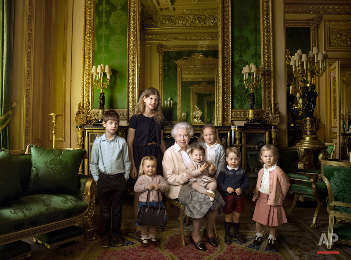 This official photograph, released by Buckingham Palace on Wednesday April 20, 2016, to mark her 90th birthday, shows Queen Elizabeth II with her five great-grandchildren and her two youngest grandchildren in the Green Drawing Room, part of Windsor Castle's semi-State apartments in Windsor England. The children are: James, Viscount Severn, 8-years-old, left, and Lady Louise, 12-years-old, second left, the children of The Earl and Countess of Wessex; Mia Tindall, holding The Queen's handbag, the two year-old-daughter of Zara and Mike Tindall; Savannah 5-years-old, third right, and Isla Phillips, 3-years-old, right, daughters of The Queen's eldest grandson Peter Phillips and his wife Autumn; Prince George, 2-years-old, second right, and in The Queen's arms and in the tradition of Royal portraiture, the youngest great-grandchild, Princess Charlotte, 11-months-old, children of Prince William and Kate Duchess of Cambridge. (© 2016 Annie Leibovitz via AP)
