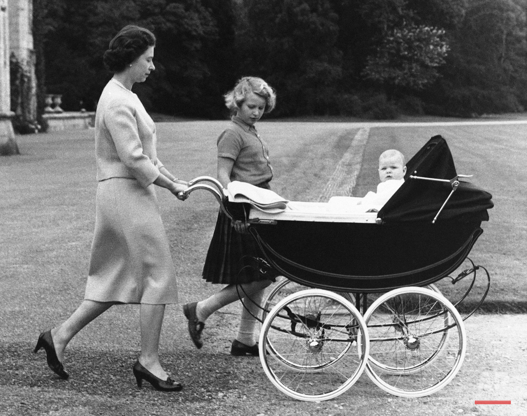 Queen Elizabeth II of Great Britain strolls in the grounds of her Scottish home in Balmoral castle, Scotland, Sept. 13, 1960, with Princess Anne and Prince Andrew in the perambulator. (AP Photo)