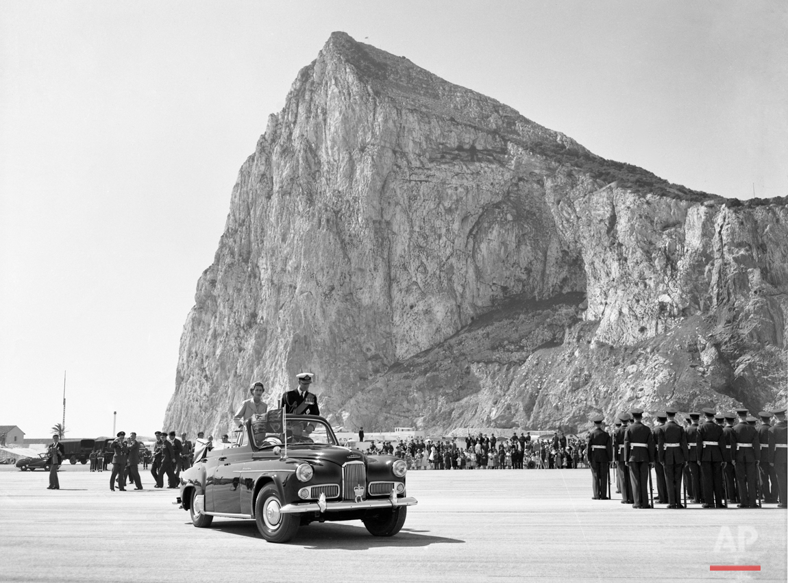 The Rock towers over Britain's Queen Elizabeth II, and the Duke of Edinburgh drive past the assembled ranks of troops and lines of bombers, during a review of the services at North Front Airfield after they had arrived in Gibraltar, on May 10, 1954. (AP Photo/Worth)
