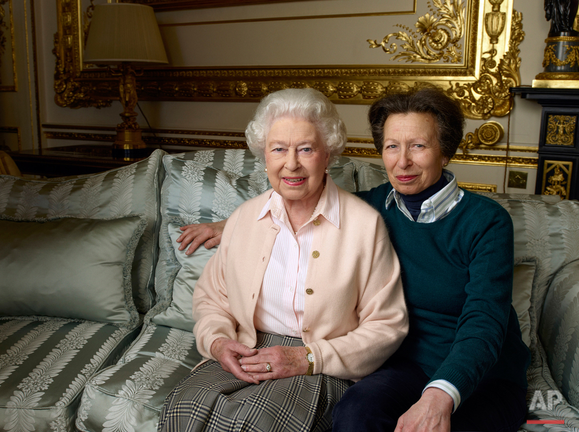 In this official photograph released by Buckingham Palace on Wednesday April 20, 2016 to mark her 90th birthday, Queen Elizabeth II is pictured with her daughter, The Princess Royal, in the White Drawing Room at Windsor Castle in England. (© 2016 Annie Leibovitz via AP)