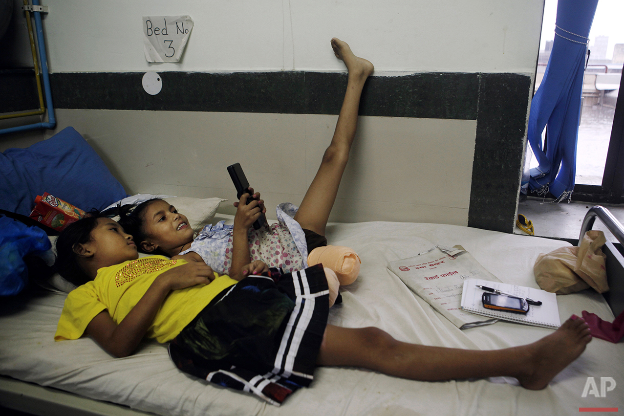 In this July 6, 2015, photo, Nepalese amputee victims and best of friends, Khendo Tamang, left, and Nirmala Pariyar, both 8, play on a mobile phone at the Bir Trauma Center in Kathmandu, Nepal. Each girl lost one leg in Nepal's massive April 25, 2015 earthquake that killed nearly 9,000 people and injured more than 22,000. (AP Photo/Niranjan Shrestha)