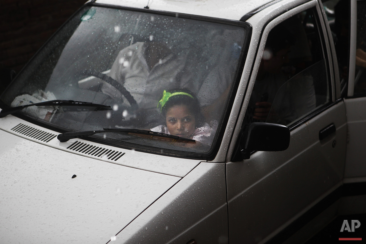 In this Aug.19, 2015 photo, Nirmala Pariyar, 8, looks out a car window after her best friend Khendo, also 8, was dropped off at a relative's house. Both girls had grown inseparable after each lost a leg in the massive 2015 Nepal earthquake and spent the following months in recovery together. (AP Photo/Niranjan Shrestha)