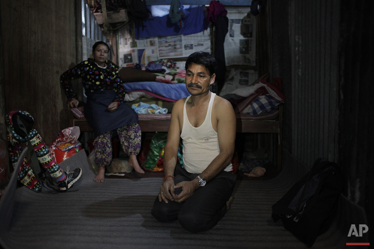 In this March 25, 2016 photo, Chitra Bahadur, foreground, and Maya Pariyar, both parents of Nepal's 2015 earthquake amputee victim Nirmala Pariyar, 8, sit in a makeshift room in a small textile factory in Kathmandu, Nepal.  While on a visit to her father Chitra in Kathmandu, Nirmala was at a neighbor's home watching TV when the quake hit, causing the house to collapse around her. (AP Photo/Niranjan Shrestha)