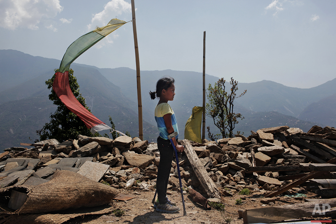 In this April 8, 2016 photo, Khendo Tamang, 8, stands near the debris of the collapsed home she was trapped in after the April 25, 2015 earthquake struck in Banskharka, Nepal. Khendo was in a packed house with her grandmother, sister and many other villagers discussing ways to alleviate their poverty. When the quake struck, the house collapsed, killing her grandmother and her sister and leaving Khendo with severe leg injuries. (AP Photo/Niranjan Shrestha)