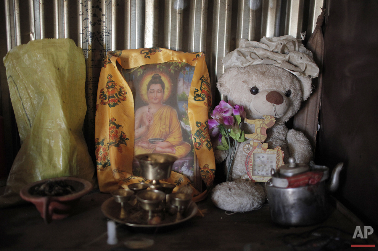 In this April 8, 2016 photo, a teddy bear and the image of Buddha are placed inside the makeshift shelter of Khendo Tamang's grandfather in Banskharka, Nepal. Khendo, 8, lost a leg in Nepal's massive 2015 earthquake. (AP Photo/Niranjan Shrestha)
