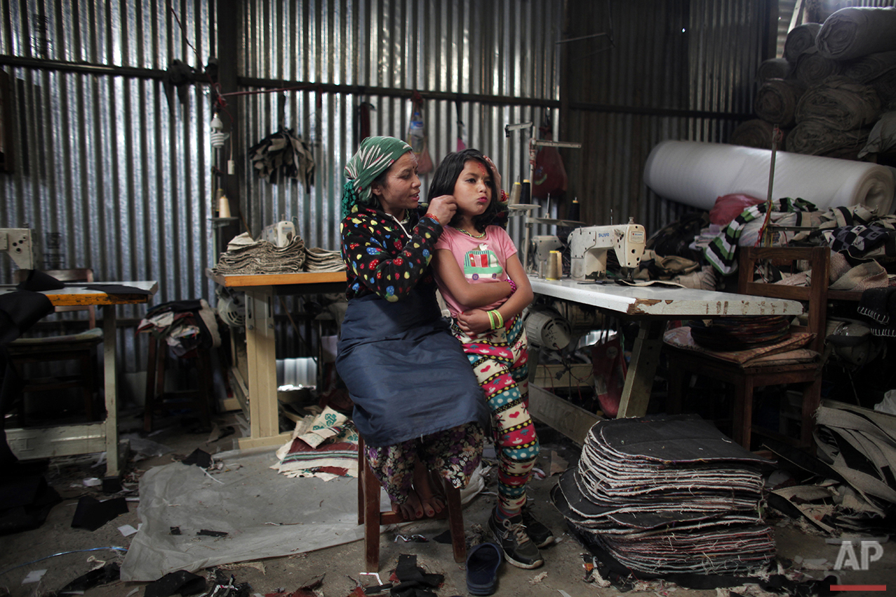 In this March 28, 2016 photo, Maya Pariyar, 39, styles the hair of her daughter Nirmala, 8, at a textile factory in Kathmandu, Nepal. Nirmala, an amputee victim in Nepal's massive 2015 earthquake, has not been in school for a year now, something that deeply worries her parents. The high costs of $1,300 per year for her to go to school in Kathmandu are just unimaginable for her parents. (AP Photo/Niranjan Shrestha)