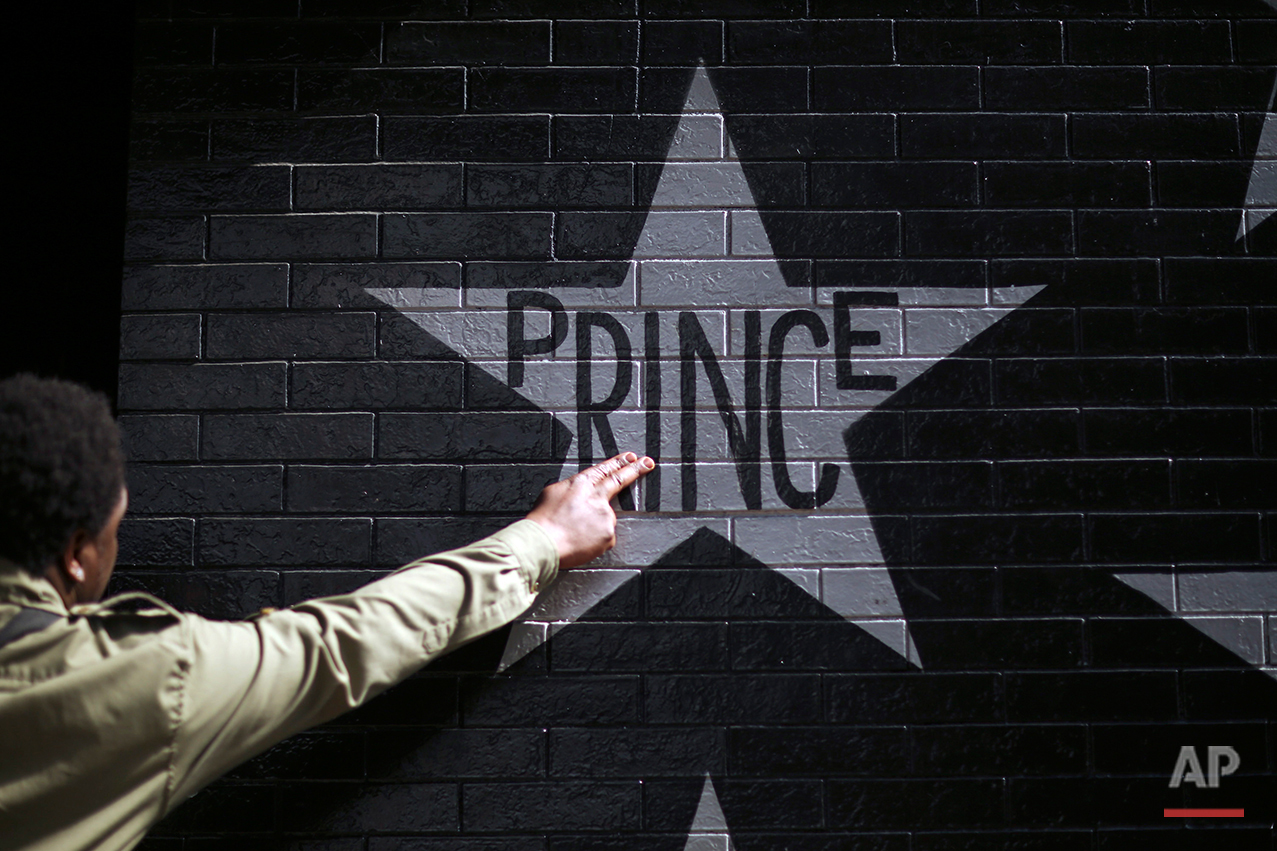 "After kissing his fingers, a fan touched Prince's star on the wall of First Ave., Thursday, April 21, 2016. Prince, widely acclaimed as one of the most inventive and influential musicians of his era with hits including ""Little Red Corvette,"" ''Let's Go Crazy"" and ""When Doves Cry,"" was found dead at his home on Thursday, according to his publicist. He was 57.  (Jeff Wheeler/Star Tribune via AP)"