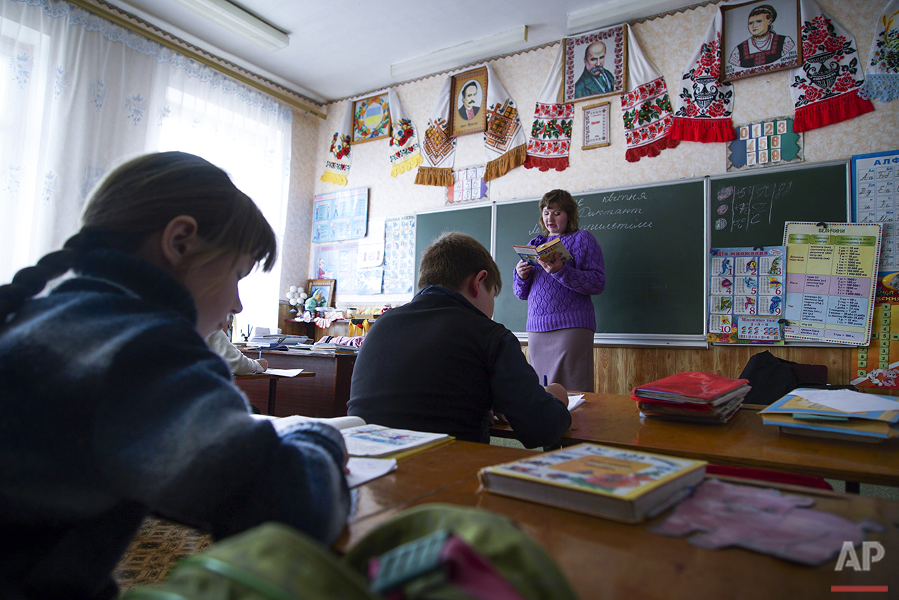 In this photo taken on Tuesday, April  5, 2016, teacher Natalya Stepanchuk, background center, reads, while children write during a lesson in a school in Zalyshany, 53 km (32 miles) southwest of the destroyed reactor of the Chernobyl plant, Ukraine. (AP Photo/Mstyslav Chernov)