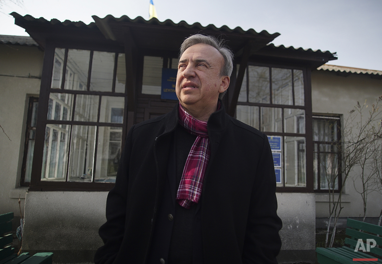 In this photo taken on Tuesday, April  5, 2016, Yuri Bandazhevsky, a pediatrician who has been studying the effect of small doses of radiation on the human body, stands outside a hospital in Ivankiv, Ukraine. Bandazhevsky, whose work is widely cited abroad, was imprisoned in his native Belarus for four years. Supporters alleged it was due to his work on studying Chernobyl's consequences; he now works in Ukraine.  (AP Photo/Mstyslav Chernov)