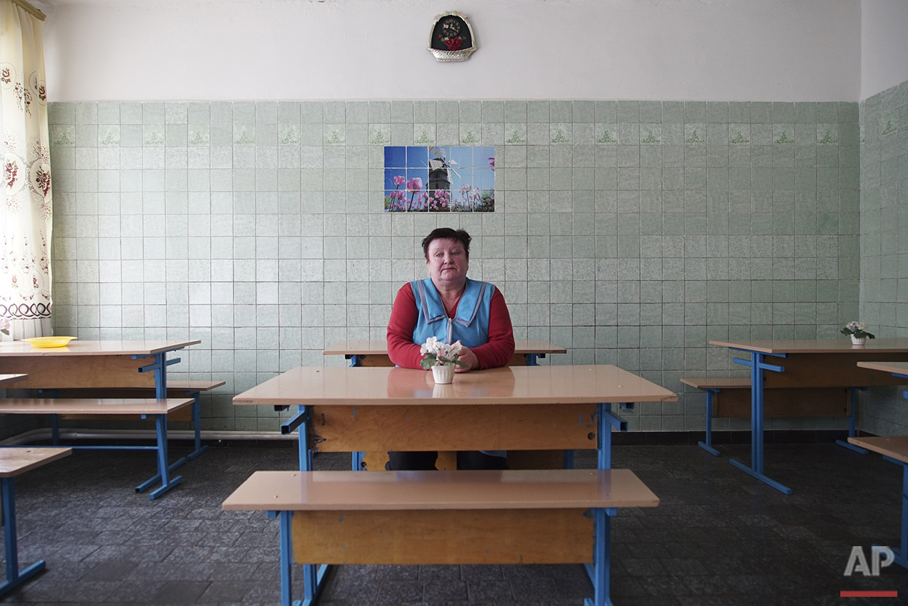 In this photo taken on Tuesday, April  5, 2016, kindergarten's cook Lyubov Shevchuk sits at the empty table of a canteen, where children used to have lunch before it was canceled, in Zalyshany, 53 km (32 miles) southwest of the destroyed reactor of the Chernobyl plant, Ukraine. (AP Photo/Mstyslav Chernov)
