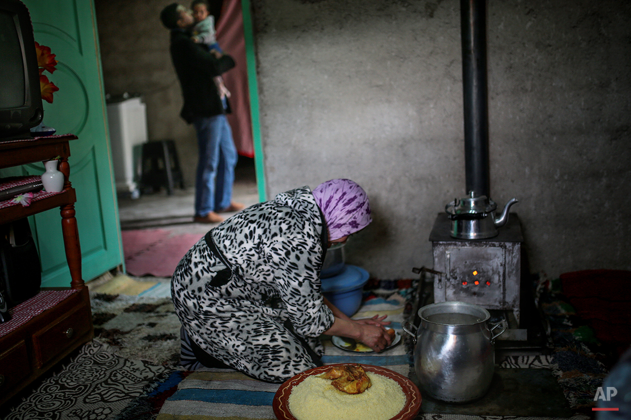 In this Friday, Feb. 5, 2016 photo, Fatima, 36, prepares a meal of Couscous, a traditionally Amazigh dish, as her husband, Mohamed looks after their daughter Sayeda, 3, at their home in a town near Tounfit in the Middle Atlas, central Morocco. Today the Amazigh rely on cattle and agriculture as their main sources of income and maintain a nomadic lifestyle closely resembling that of their ancestors. Some live in clay houses with no electricity or running water while a few still dwell with their sheep and goats in remote mountain caves. Others live closer to the towns at the Atlas foothills, benefiting from modern amenities. (AP Photo/Mosa'ab Elshamy)
