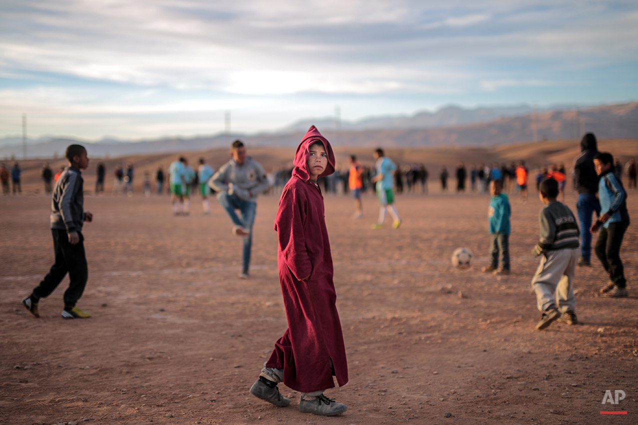 In this Wednesday, Feb. 3, 2016 photo, an Amazigh boy pauses to look at the camera during a locally-organized football tournament between different tribes, in Kelaat M'Gouna town, southern Morocco. Across North Africa, the Berbers number about 50 million. At least 15 million Moroccans are Amazigh, divided into different groups according to their dialects. While they speak the native Amazigh language of Tamazight, which has a large number of dialects and recently gained recognition as an official language in Morocco, many have adopted Arabic as part of a long process of Arabization and Islamization. (AP Photo/Mosa'ab Elshamy)