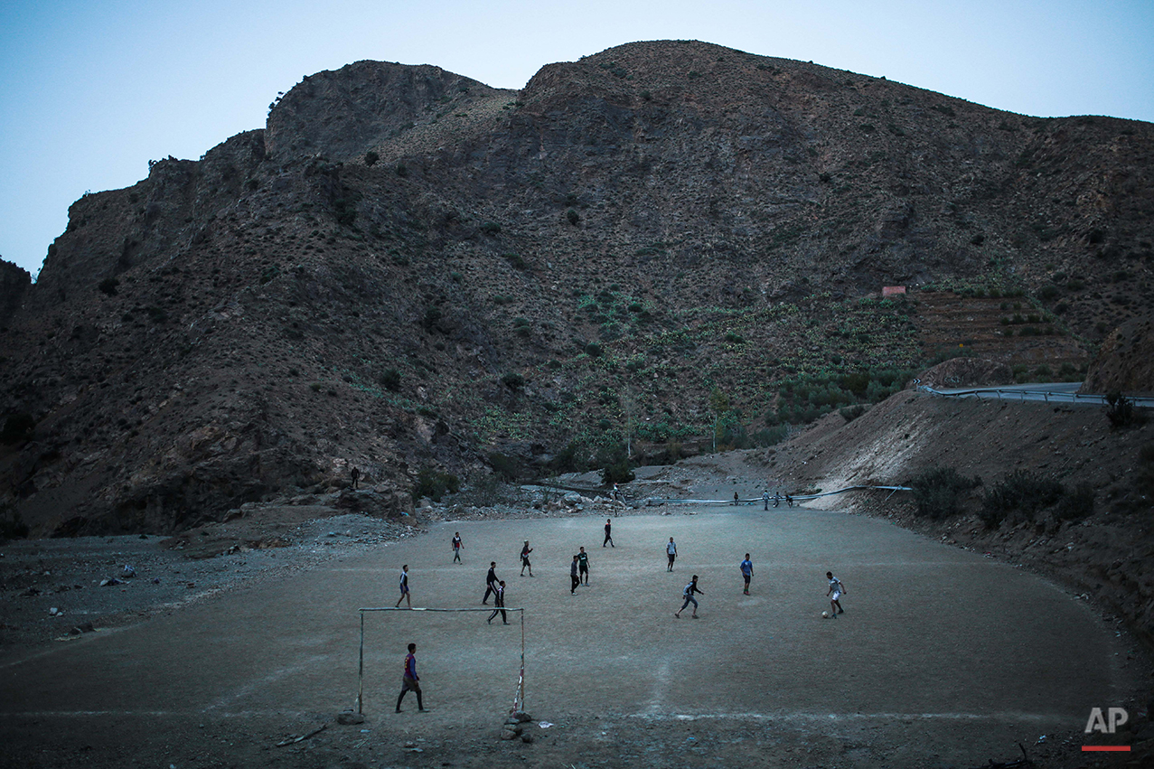 In this Monday, Feb. 1, 2016 photo, Amazigh boys play football underneath the High Atlas mountains, near Ouarzazate, central Morocco. Across North Africa, the Berbers number about 50 million. At least 15 million Moroccans are Amazigh, divided into different groups according to their dialects. While they speak the native Amazigh language of Tamazight, which has a large number of dialects and recently gained recognition as an official language in Morocco, many have adopted Arabic as part of a long process of Arabization and Islamization. (AP Photo/Mosa'ab Elshamy)
