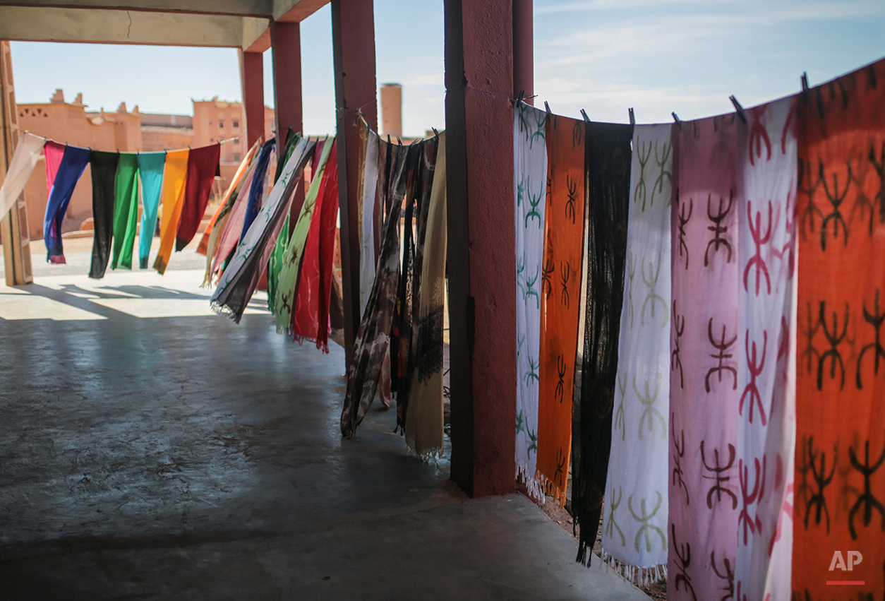 In this Wednesday, Feb. 3, 2016 photo, scarves with the Amazigh symbol are displayed outside a tourist shop, in Kalaat M'Gouna, in Ouarzazate, Morocco. Across North Africa, the Berbers number about 50 million. At least 15 million Moroccans are Amazigh, divided into different groups according to their dialects. While they speak the native Amazigh language of Tamazight, which has a large number of dialects and recently gained recognition as an official language in Morocco, many have adopted Arabic as part of a long process of Arabization and Islamization. (AP Photo/Mosa'ab Elshamy)