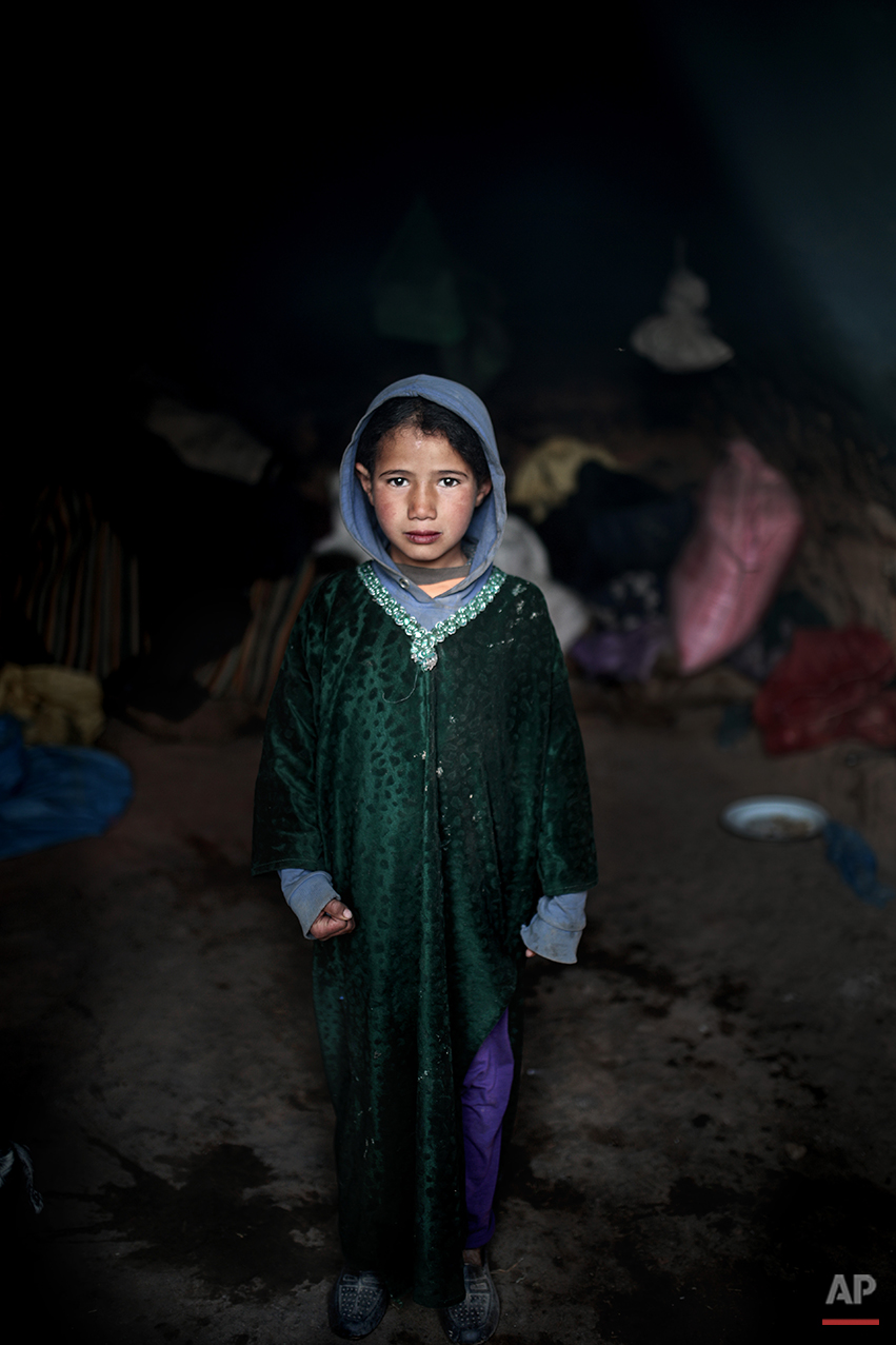 In this Thursday, Feb. 4, 2016 photo, Fatima, 5, poses for a picture inside a cave where she lives with her family, in the desert of the Anti-Atlas mountains, east of Ourazazate, Morocco. The Amazigh dislike the term Berbers, which stems from Latin and which they find insulting. They are among the many peoples the Romans called Barbarians but they became the stuff of legends, giving the world famous names such as the medieval explorer Ibn Battuta, who travelled further in distance than Marco Polo. (AP Photo/Mosa'ab Elshamy)